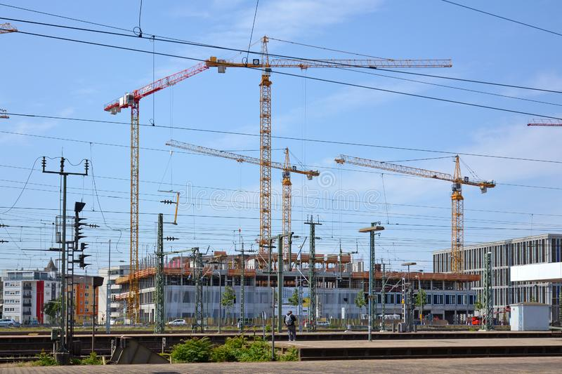 Big construction area surrounded by multiple orange tower cranes next to main station royalty free stock photos