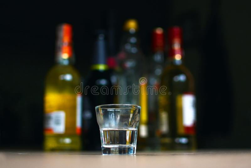 Empty small shots glass in front of multiple blurry different strong spirits alcohol bottles in darkbackground. Mannheim, Germany - June 2019: Empty small shots stock photography