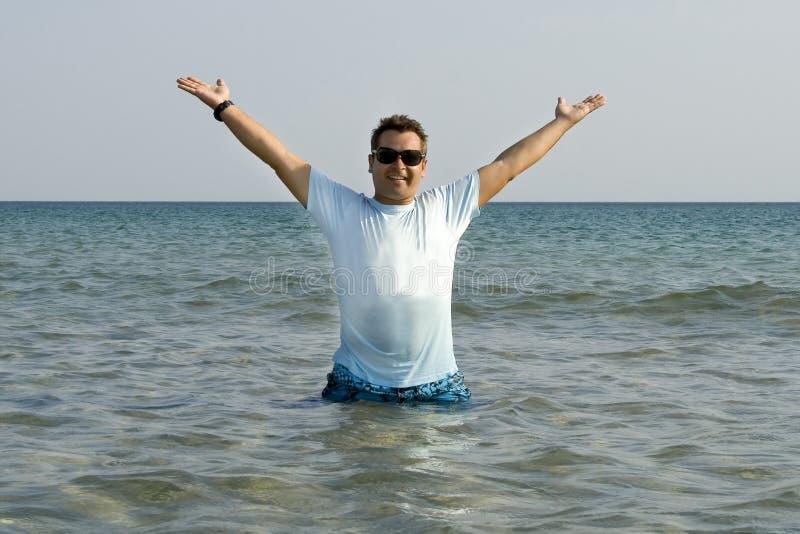 Mannherausspringen des Meeres mit Spritzen lizenzfreie stockfotos