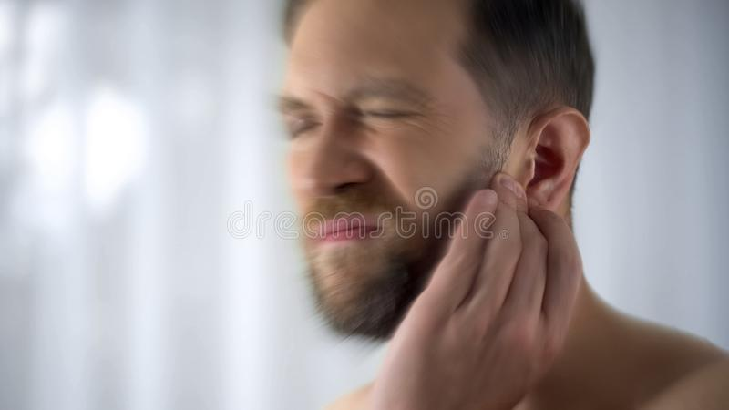 Mannholding, die oben Ohr-, Mittelohrentzündungs- oder Infektionsfacharzt- für hals- und ohrenleidenprobleme, Abschluss verletzt stockbilder
