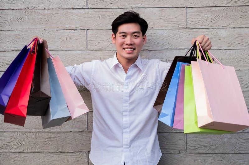 Mannholding-Einkaufstascheblick auf Kamera und Lächeln, Einkaufskonzept stockbild