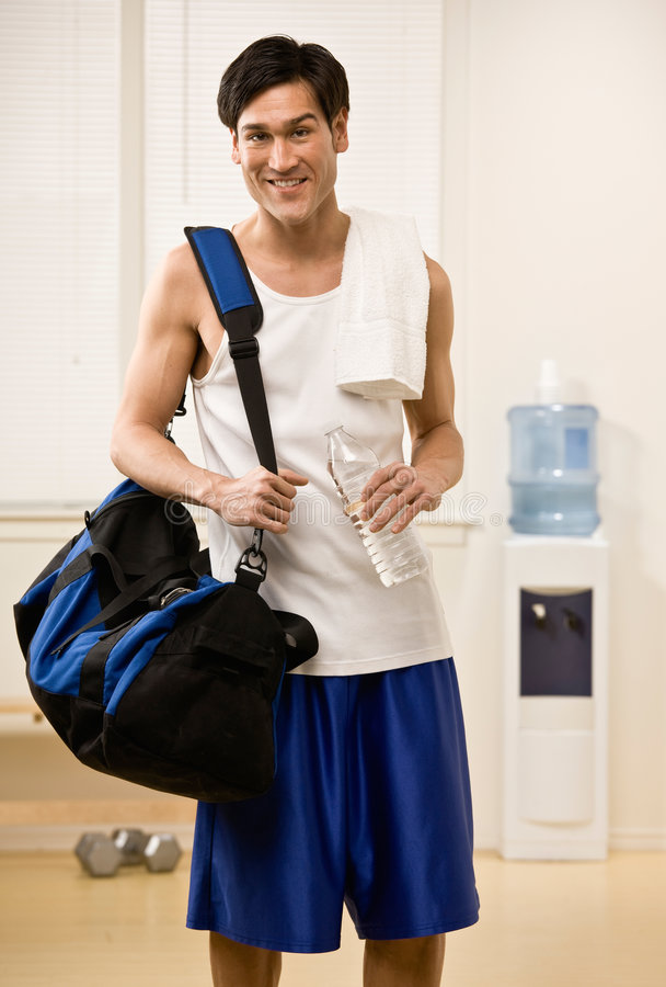 Mannholding-Gymnastikbeutel und Wasserflasche stockfoto