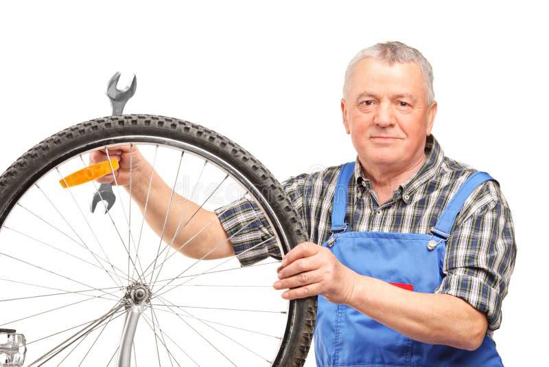 Mannholdingschlüssel und Reparatur des Fahrradrades stockfotografie