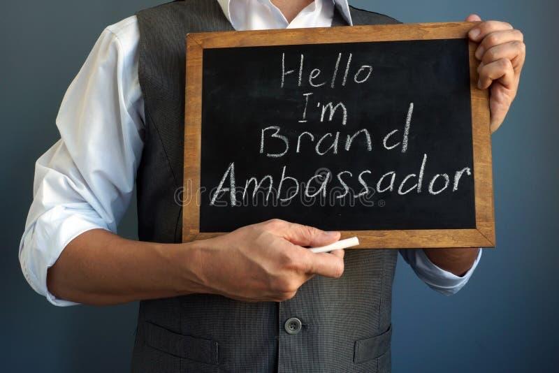 Mannholdingtafel mit Zeichen bin ich Marken-Botschafter lizenzfreies stockfoto