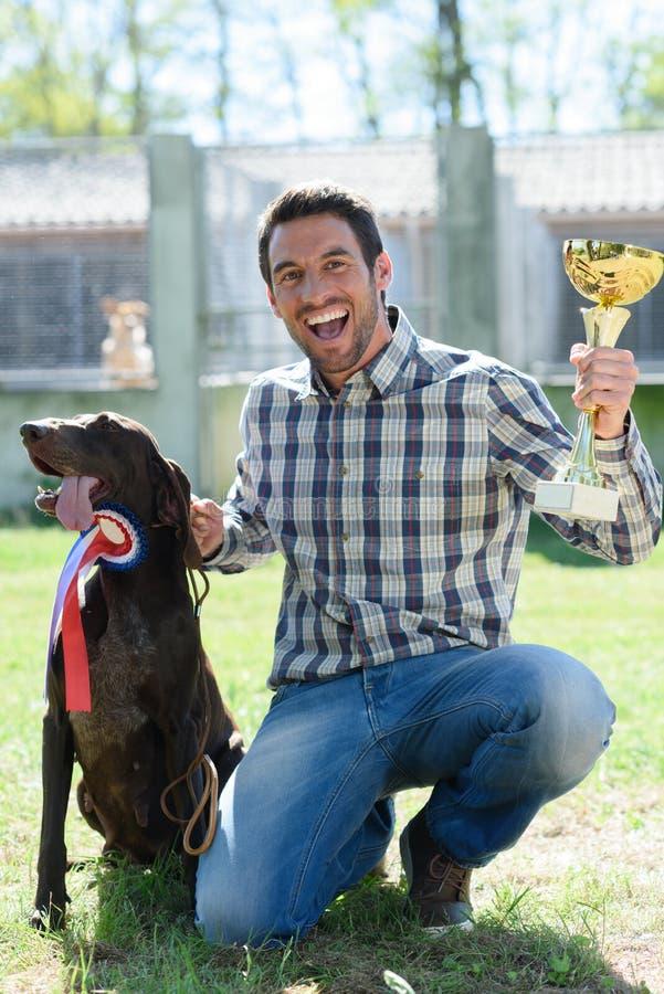 Mannholdingtrophäe mit Hund auf Seite stockbilder