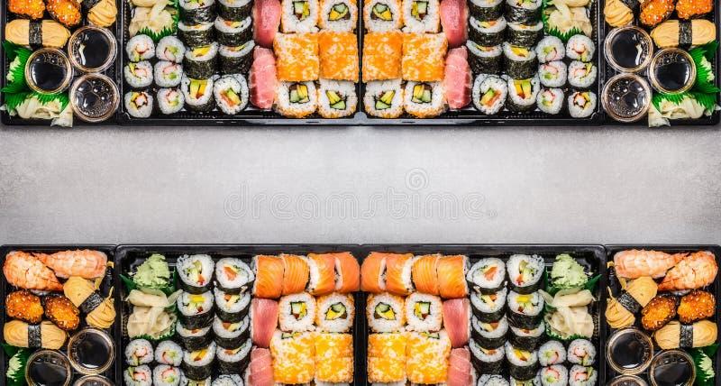Mannigfaltiges Sushi stellt Zusammenstellung in bento Kästen auf grauem Steinhintergrund, Draufsicht ein stockfotografie