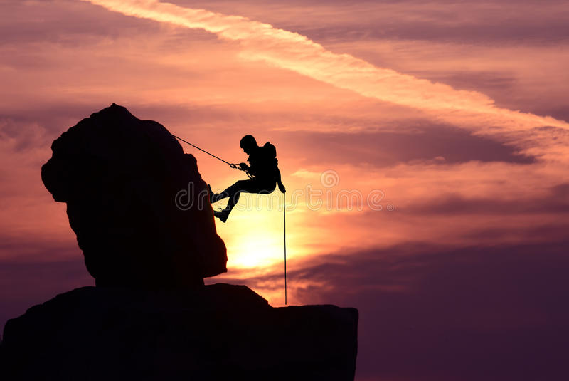 Mannklettererschattenbild über hellem Sonnenuntergang stockfoto