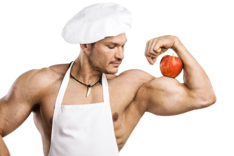 Mannkoch - Bodybuilder mit Apfel auf Bizeps lizenzfreies stockbild
