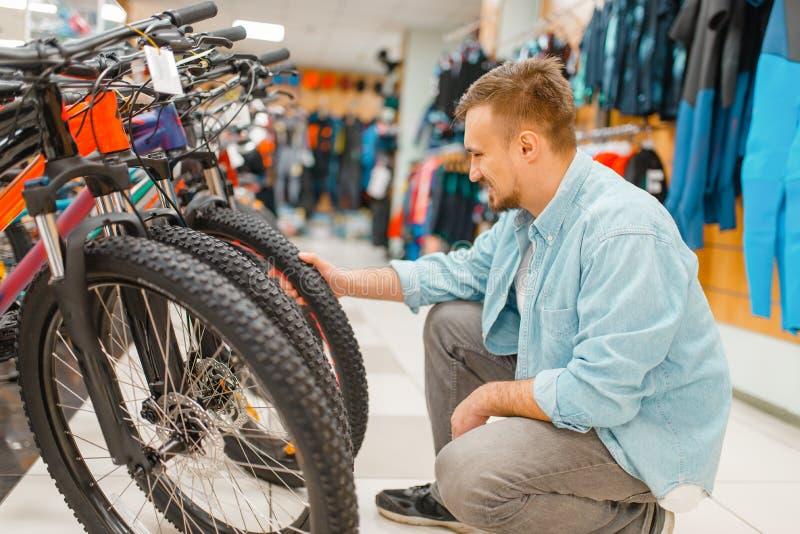 Mannkontrollen fahren Reifen, Einkaufen im Sportgeschäft rad stockbilder
