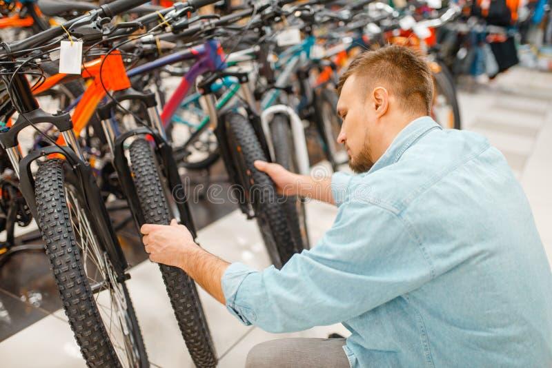 Mannkontrollen fahren Reifen, Einkaufen im Sportgeschäft rad lizenzfreie stockfotografie