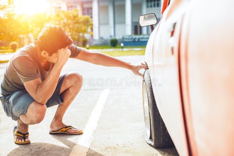 Mannkopfschmerzen wenn Autozusammenbruch und Flachstellereifen auf der Straße im Parken lizenzfreies stockfoto