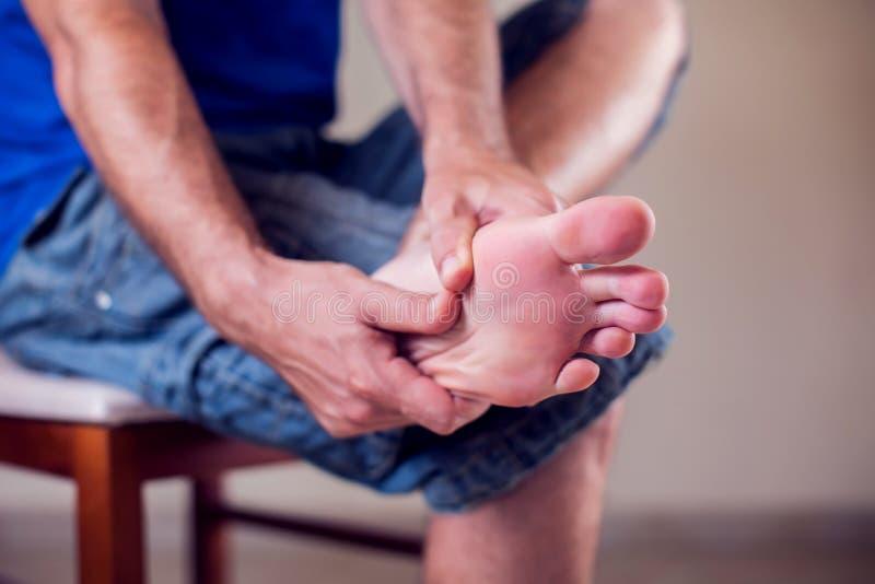 Mannleiden von den Fußschmerz, die auf Bank auf Straße sitzen Leute, Gesundheitswesen, Medizinkonzept stockfotografie