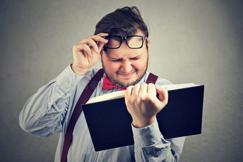 Mannlesebuch mit schlechtem Sehvermögen lizenzfreie stockfotografie