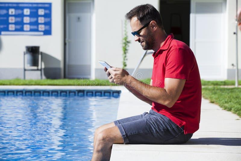 Mannlesetablette, die auf dem Poolside sitzt stockbilder