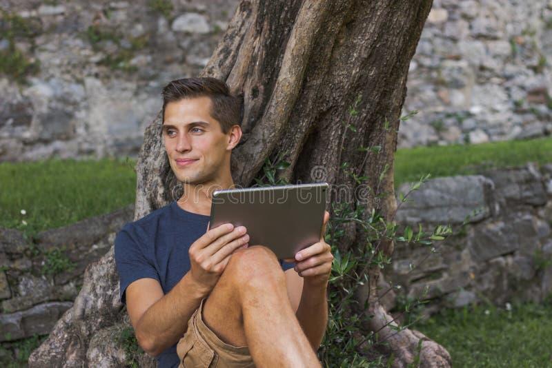 Mannlesetablette und Rest in einem Park unter Baum genie?en lizenzfreie stockfotos