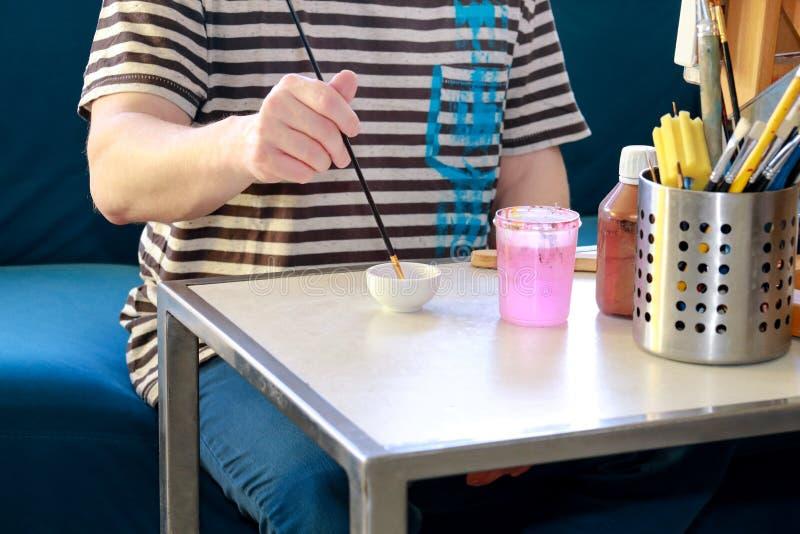 Mannmaler mischt Farben vor Malerei am Kunstfarbenstudio Künstler in seinem Handholdingmalerpinsel mischte Farbölfarben stockbild