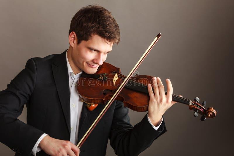 Mannmann gekleidet Violine elegant, spielend lizenzfreie stockfotografie