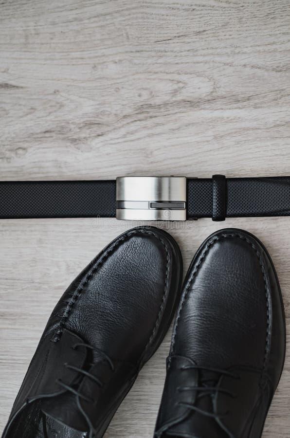 Mannmode Lokalisiert auf Weiß Schwarze Schuhe und schwarzer Gürtel Noch Leben 1 Geschäftsblick auf einem hölzernen Hintergrund lizenzfreies stockfoto