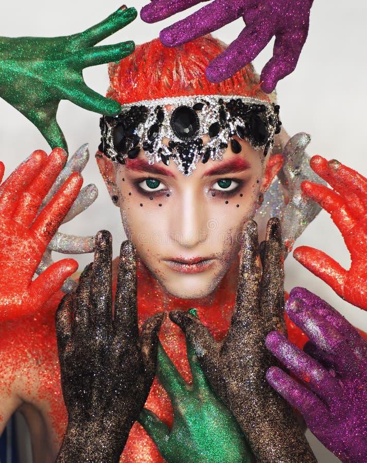 Mannmodell an der Kunst bilden mit den grünen Augen, die zur Kamera vom viele colorfull Handbesten schauen lizenzfreies stockbild