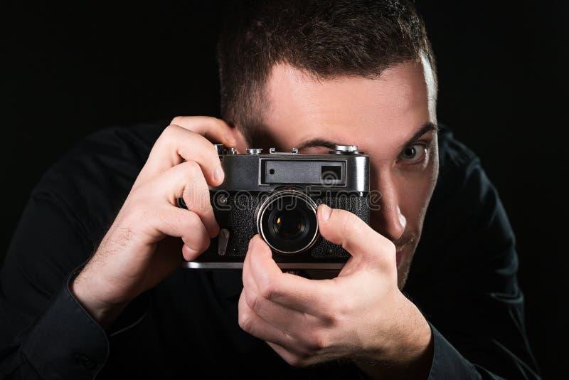 Mannphotograph, der eine Retro- Fotokamera hält Schie?enproze? Fotograf betrachtet Sucher stockbilder