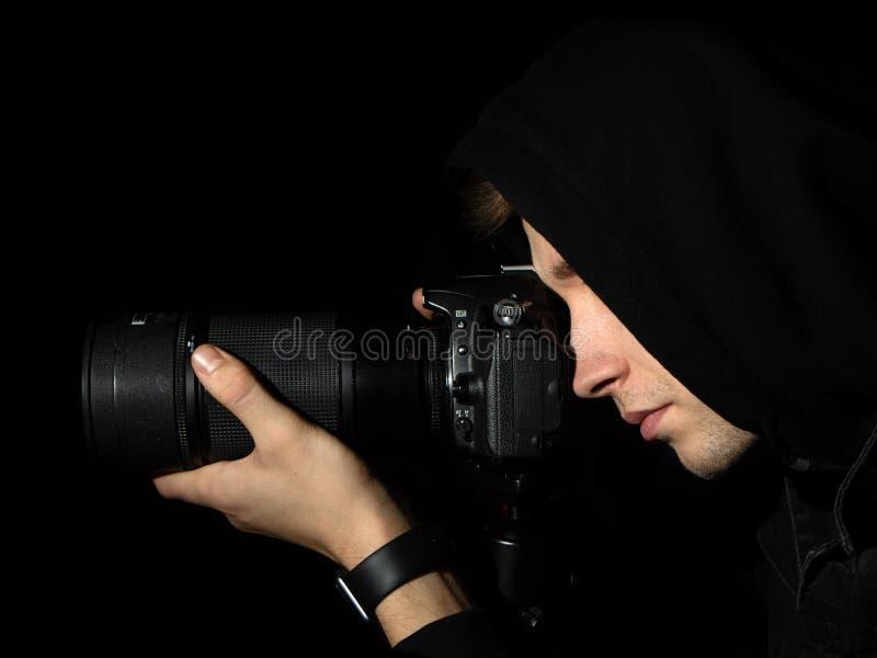 Mannphotograph mit einer DSLR-Kamera auf einem Stativ in einem schwarze Haube lokalisierten schwarzen Hintergrund stockbilder