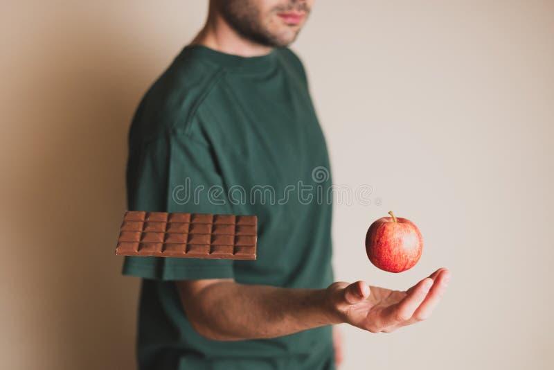 Mannplätze übergeben unter sich hin- und herbewegenden Apfel beim Ignorieren eines Schokoriegels stockbild