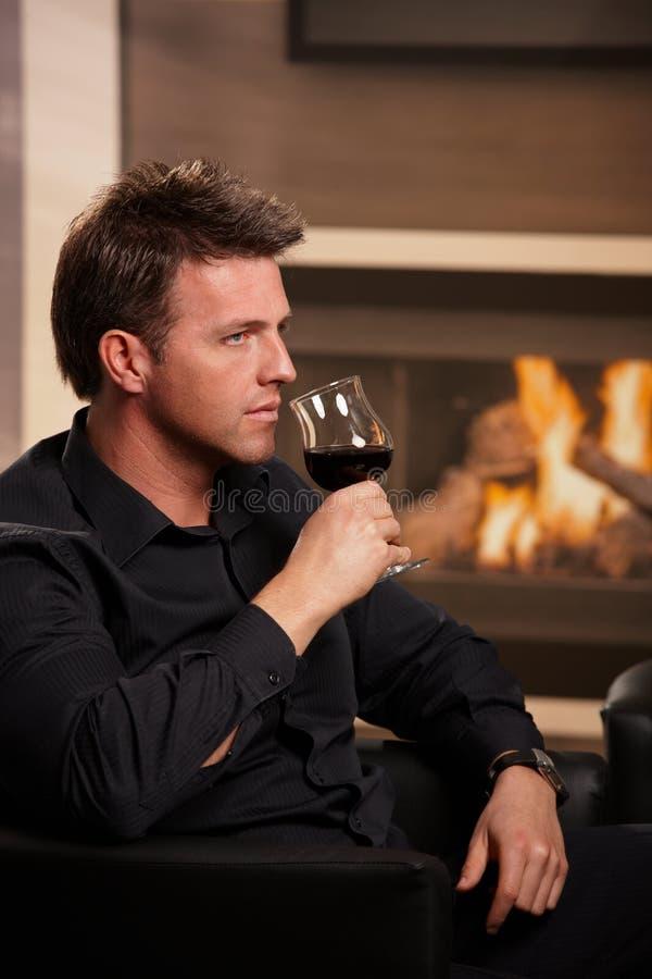 Mannprobierenwein zu Hause lizenzfreies stockbild
