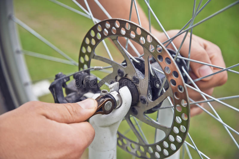 Mannradfahrer überprüft Bremsrad des Fahrrades stockbild