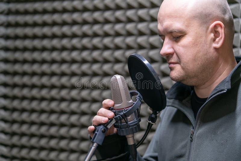 Mannradio DJ spricht in das Mikrofon in der Arbeitsplatznahaufnahme lizenzfreies stockfoto