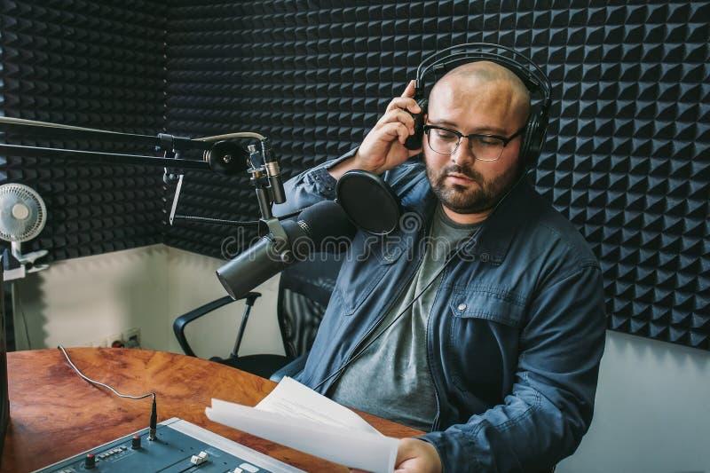 Mannradiowirt oder representer oder Journalist liest Nachrichten von der Papierliste in der Hand zum Studiomikrofon, das am Misch lizenzfreie stockfotografie