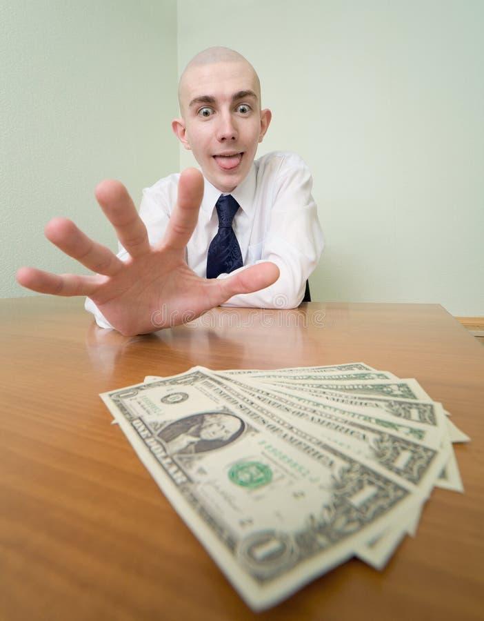 Mannreichweiten für einen Stapel des Geldes stockfotos