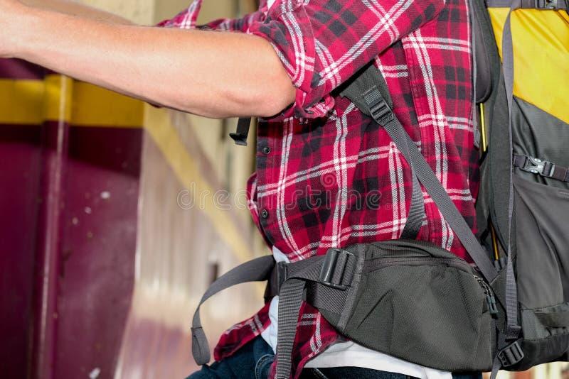 Mannreisender mit Rucksack Zug am Bahnhof steigernd stockbild