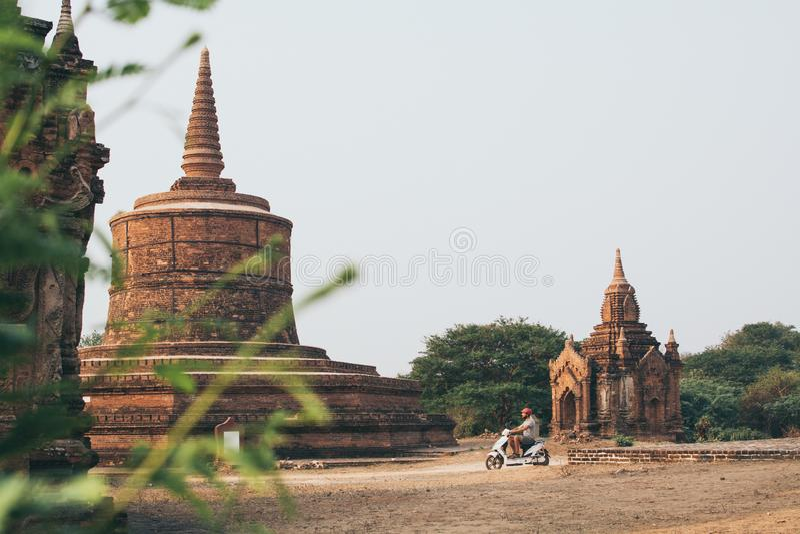 Mannreitelektrischer Roller in Richtung in Richtung den Tempeln und zu den Pagoden von altem Bagan auf Myanmar stockfotografie