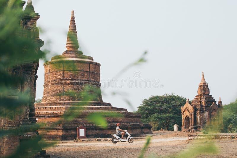 Mannreitelektrischer Roller in Richtung in Richtung den Tempeln und zu den Pagoden von altem Bagan auf Myanmar stockfotos