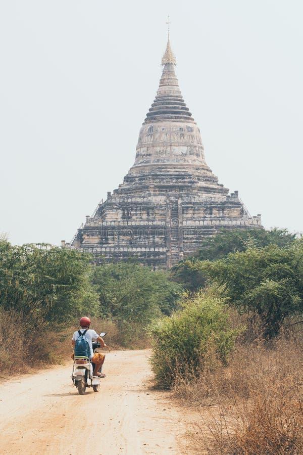 Mannreitelektrischer Roller in Richtung in Richtung den Tempeln und zu den Pagoden von altem Bagan auf Myanmar lizenzfreie stockfotografie