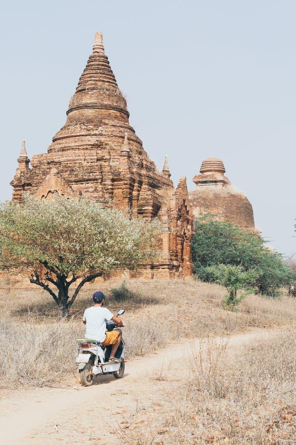 Mannreitelektrischer Roller in Richtung in Richtung den Tempeln und zu den Pagoden von altem Bagan auf Myanmar stockfoto