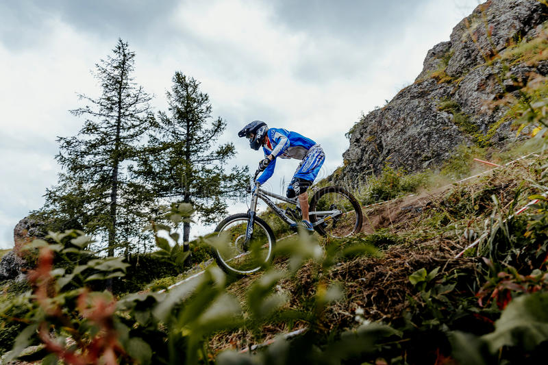 Mannreiter auf Fahrradgebirgsradfahrender Schneise lizenzfreie stockfotografie
