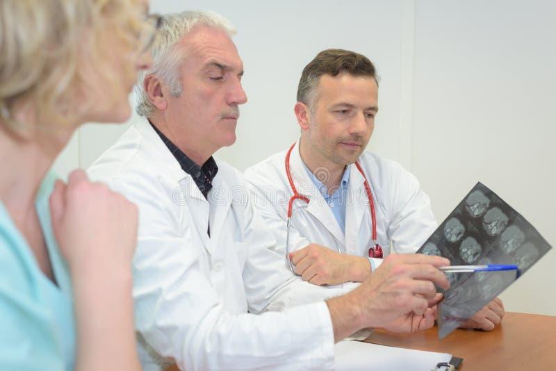 Mannschaftsärzte, die Röntgenstrahl im Konferenzzimmer betrachten stockfotografie