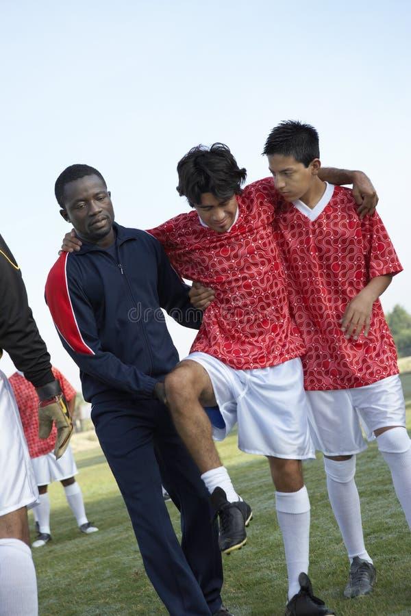 Mannschaftskameraden, die verletzten Fußball-Spieler tragen stockfoto