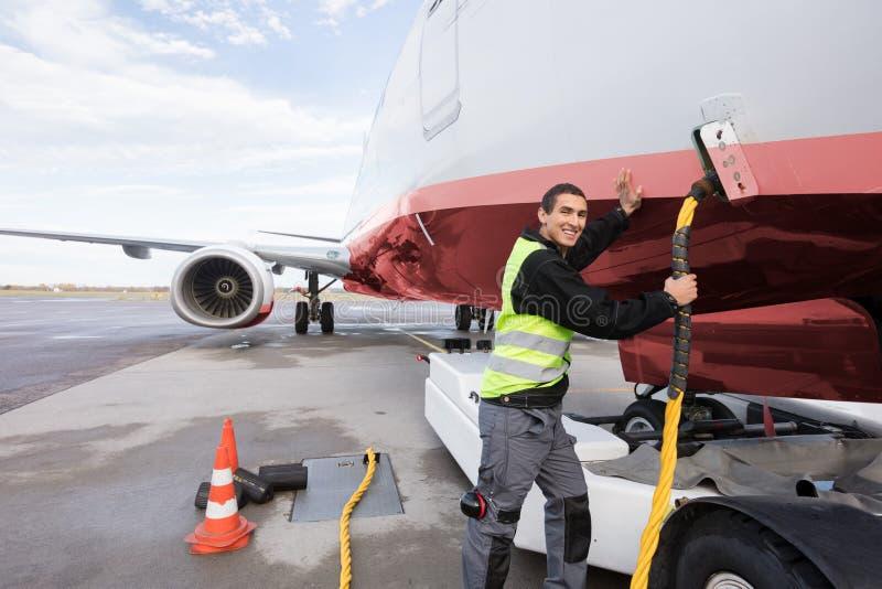 Mannschaftsmitglied-Aufladungsflugzeug auf Rollbahn lizenzfreie stockfotos