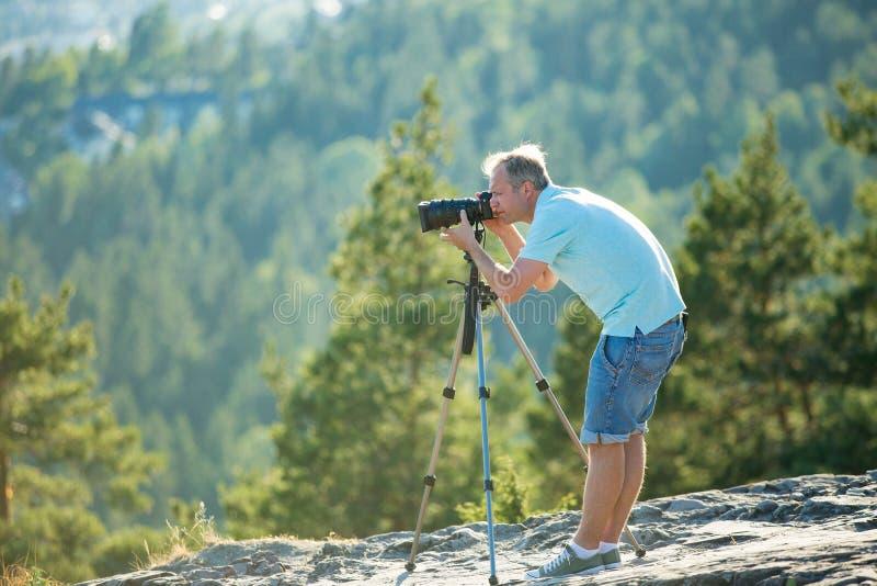 Mannschmierfilmbildung auf Kamera mit Stativ auf die Oberseite des Berges lizenzfreie stockfotos