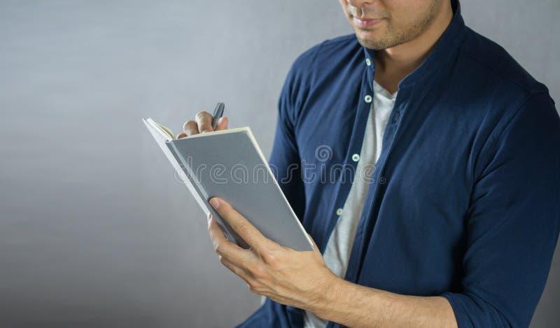Mannschreiben auf Notizbuch auf grauem Hintergrund lizenzfreie stockbilder