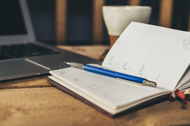 Mannschreiben in einem Notizbuch, Planungsmünder mit Laptop im Hintergrund lizenzfreies stockbild