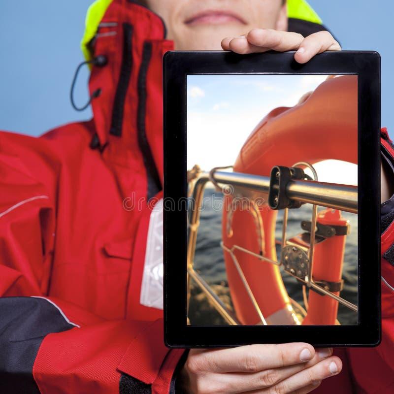 Mannseemann, der Rettungsring auf Tablette zeigt. Segeln lizenzfreie stockfotografie