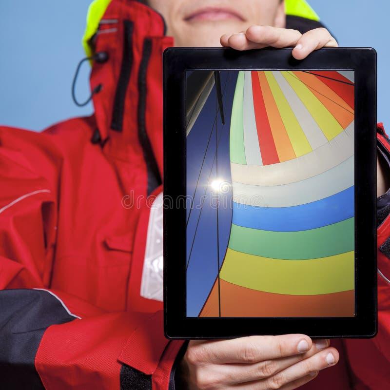 Mannseemann, der Segelboot auf Tablette zeigt segeln lizenzfreies stockbild