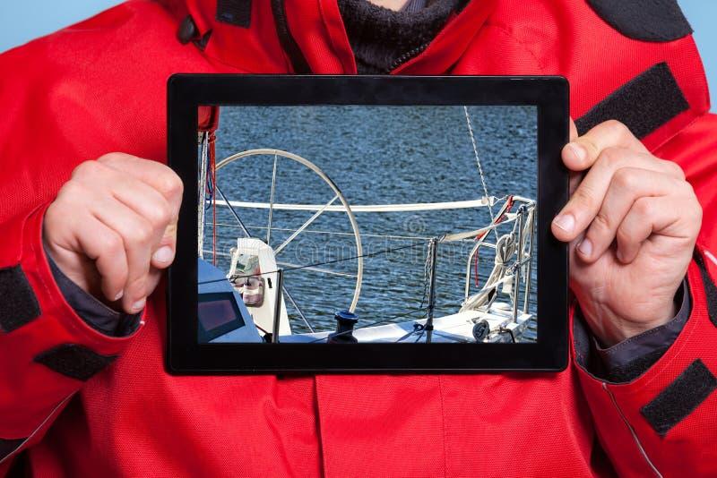 Mannseemann, der Yachtboot auf Tablette zeigt segeln lizenzfreie stockbilder