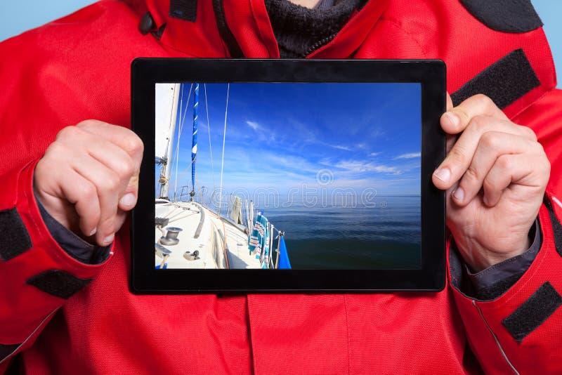 Mannseemann, der Yachtboot auf Tablette zeigt segeln stockbild