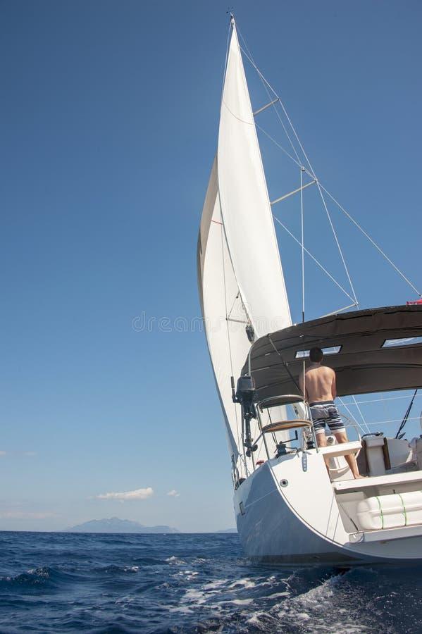 Mannsegeln in Richtung zu einer Insel in Kroatien stockfoto