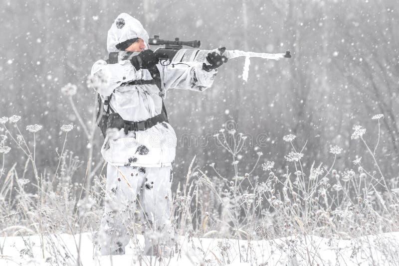 Mannsoldat im Winter auf einer Jagd mit einem Scharfschützegewehr in der weißen Wintertarnung, die Stellung im Schnee zielt stockbilder