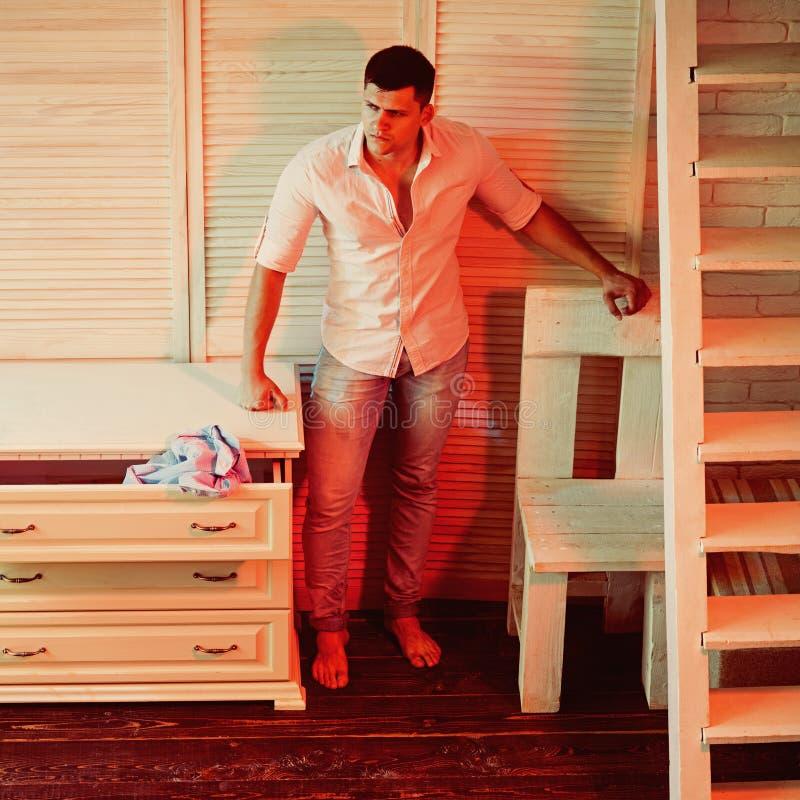 Mannstand im Rauminnenraum mit Möbeldesign Sexy Macho auf Hemd- und Jeansmode Kerl tun Wäschereihausarbeit herein lizenzfreies stockfoto